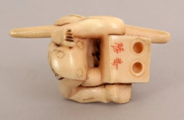 JAPANESE IVORY NETSUKE OF A STYLISED ONI 2