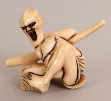 JAPANESE IVORY NETSUKE OF A STYLISED ONI